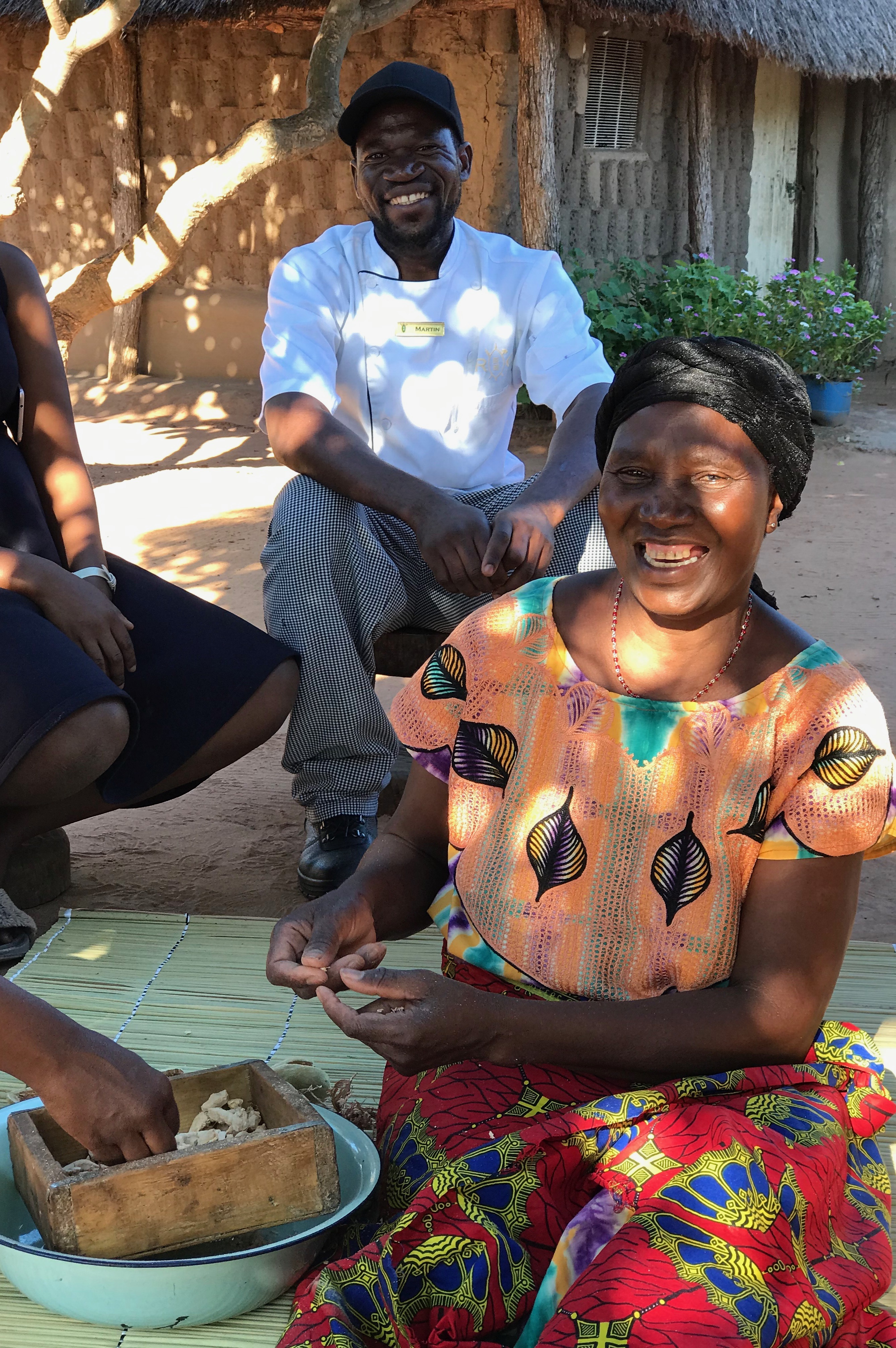 Edith Mushekwa in the process if removing the baobab powder from their pods. Her nephew, Martin, a chef at the lodge, sits behind her.