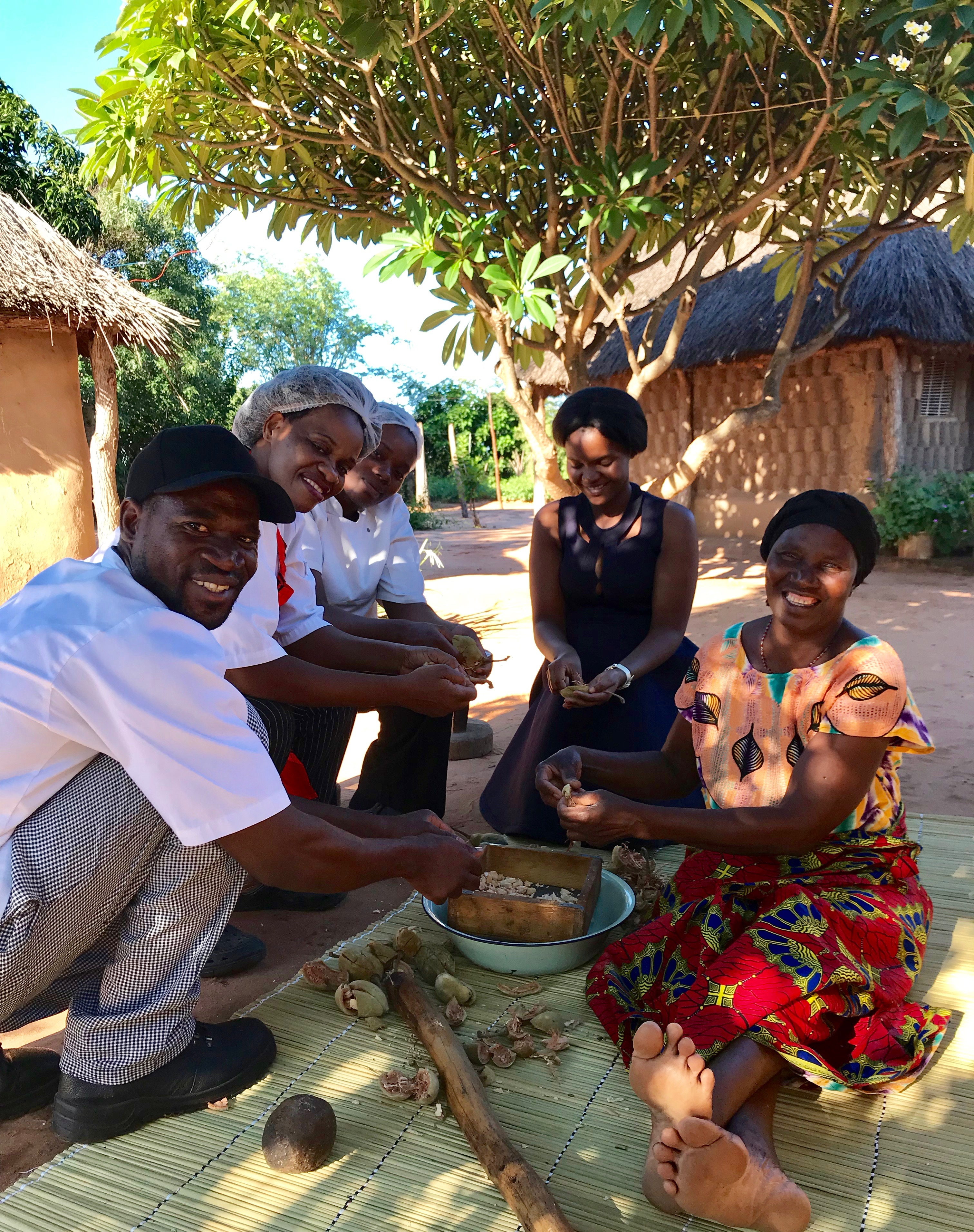 Royal Chundu's chefs helping Edith Mushekwa remove the baobab powder from their pods.